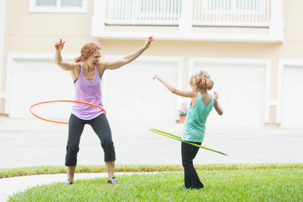 mutter und tochter mit hula hoops - hula hoop workout stock-fotos und bilder