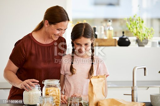 Happy mother and daughter with jars and paper bags in kitchen. Mature woman and girl are smiling while standing at home. They are wearing casuals.