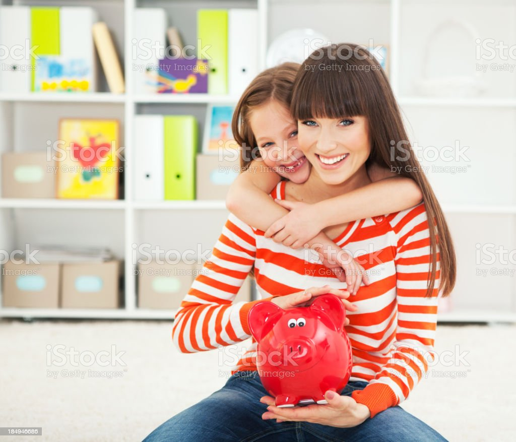 Mother and daughter with piggy bank. royalty-free stock photo