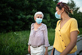 istock Mother and daughter with protective face mask, walking down street and talking 1264500902