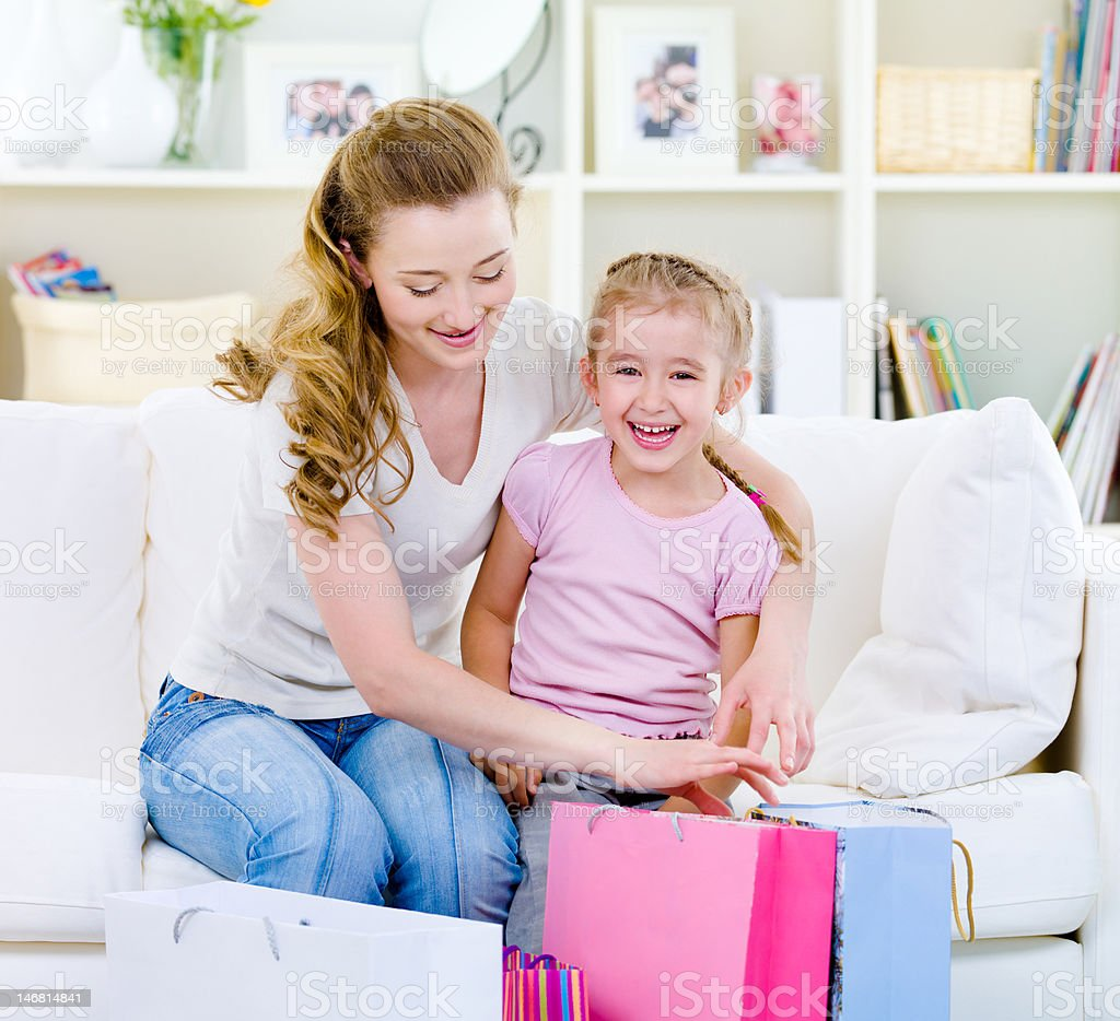 Mother and daughter with shopping bags at home royalty-free stock photo