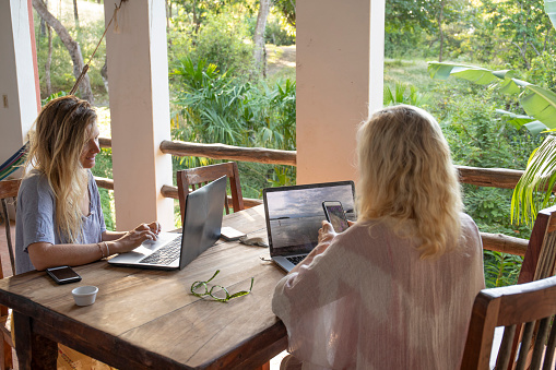 Mother and daughter work from tropical home in the morning