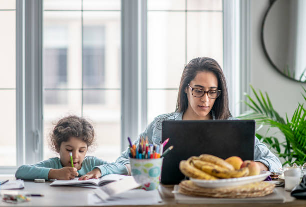 Mother and daughter working from home. stock photo