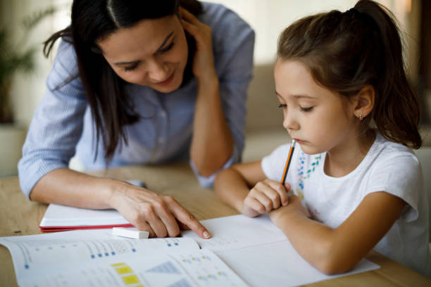 Mother and daughter working homework together stock photo