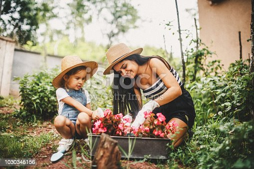 Mother And Daughter Working In The Garden