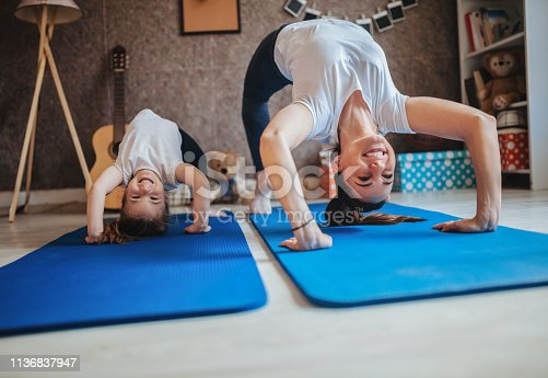 istock Mother and daughter working out together doing exercise at home 1136837947