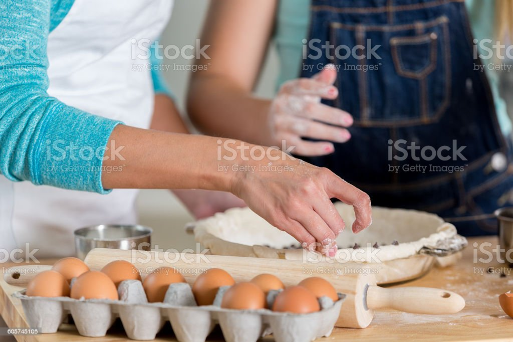 Mother and daughter working with dough to bake a pie stock photo