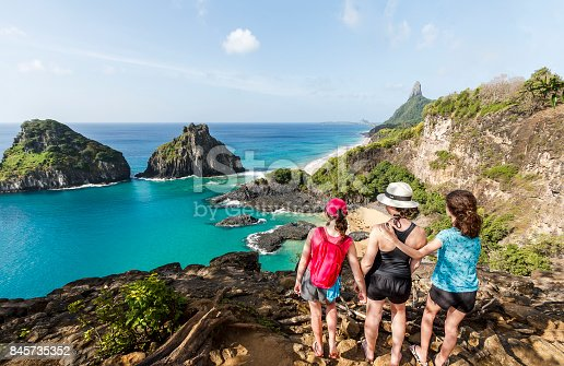 A DSLR Canon photo of a mother and her two daughters standing at the top of a cliff watching Two Brothers mountain, the main natural landmark at Fernando de Noronha, Pernambuco, Brazil.