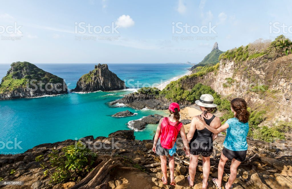 Mother and daughters at he top of a cliff in Fernando de Noronha stock photo