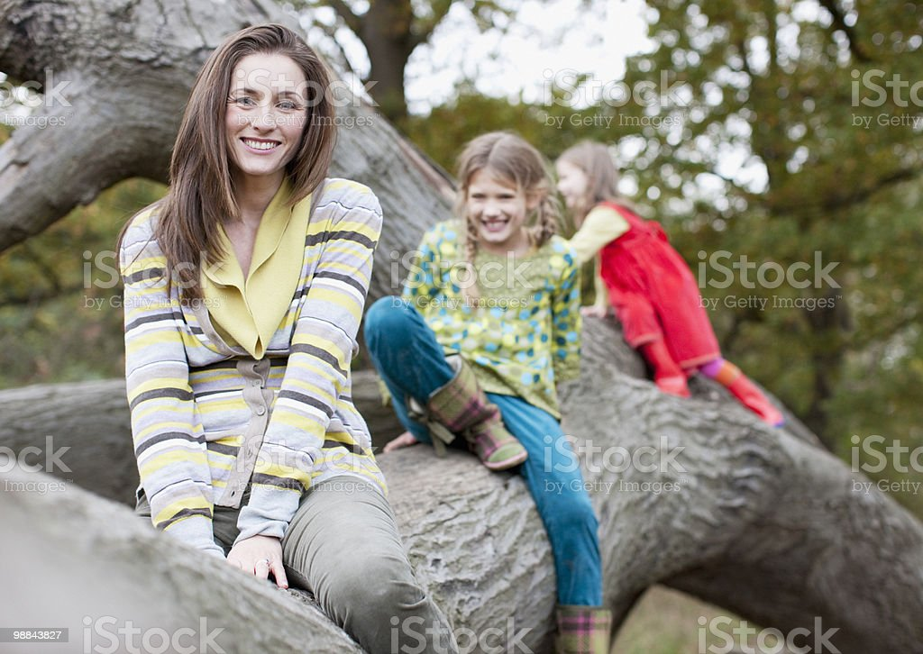 Mother and daughters climbing on tree branch royalty-free stock photo