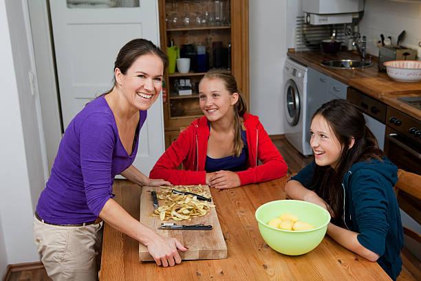 mutter und töchter kochen in der küche - peeling zu hause machen stock-fotos und bilder