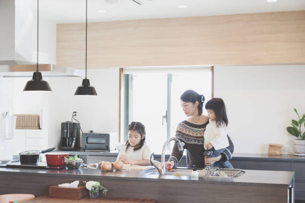 Mother and daughters cooking in the kitchen stock photo