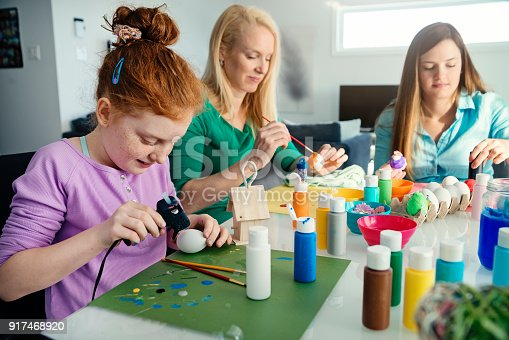 Single mother and daughters crafting some Easter decoration at home. All of them are wearing pastel colored tops. The younger one has bright red hair and freckles. Horizontal indoors waist up shot with copy space. This was taken in Quebec, Canada.