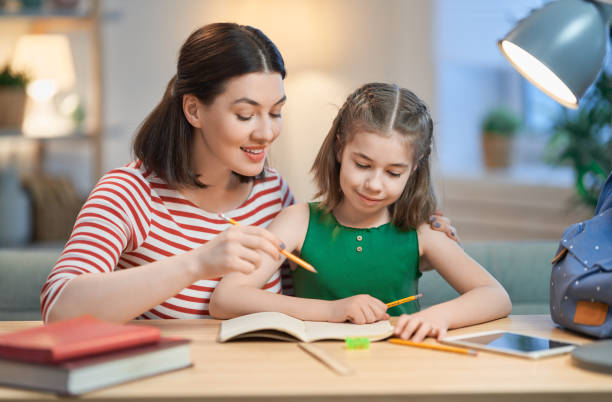 Mother and daughters drawing together stock photo