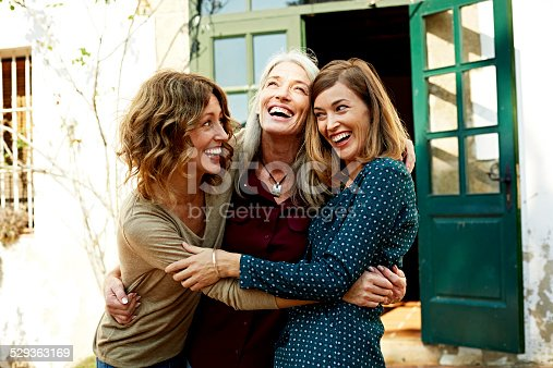 Playful mother and daughters embracing outside house