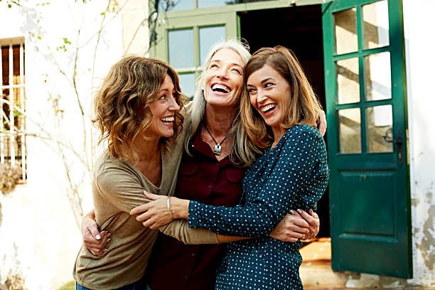 Mother and daughters embracing outdoors Playful mother and daughters embracing outside house only mature women stock pictures, royalty-free photos & images