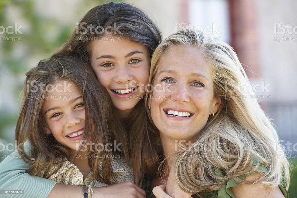 Mother and daughters hugging outdoors royalty-free stock photo
