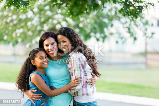 istock Mother and daughters hugging tightly and smiling at camera 598173572