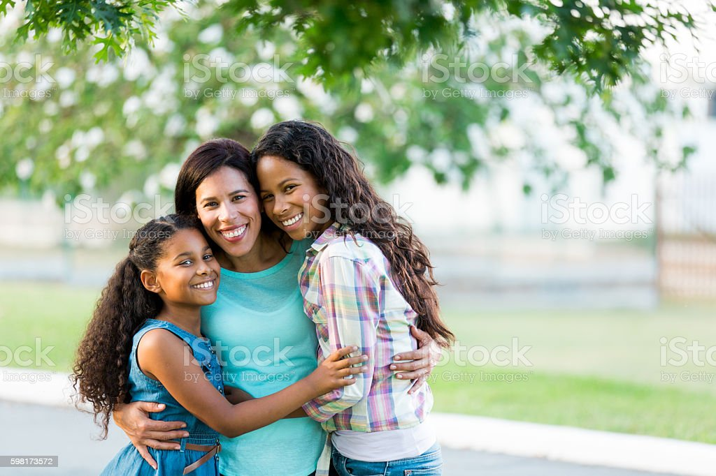 Mother and daughters hugging tightly and smiling at camera stock photo