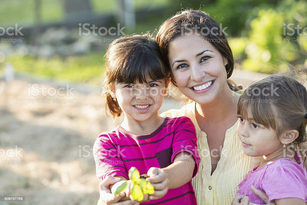 Mother and daughters in garden stock photo