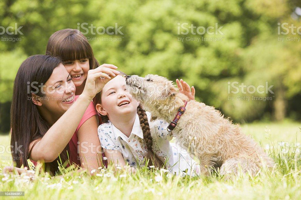 Madre e hijas con perro en el parque - Foto de stock de 20 a 29 años libre de derechos
