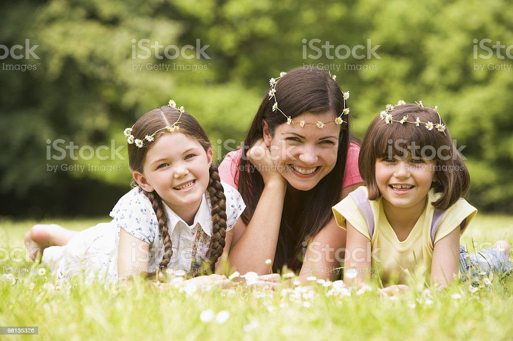Mother and daughters lying outdoors royalty-free stock photo