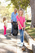 Mother And Daughters Picking Up Litter In Suburban Street Smiling