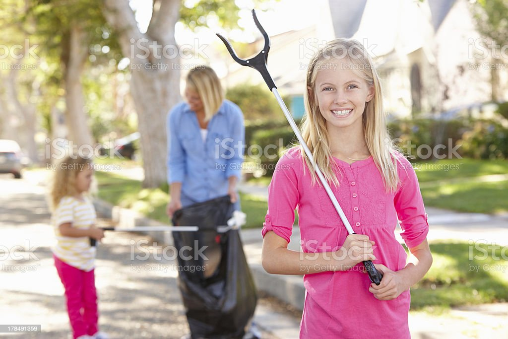 Mother And Daughters Picking Up Litter In Suburban Street royalty-free stock photo