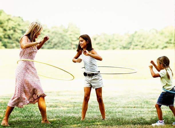 mutter und töchter - hula hoop workout stock-fotos und bilder