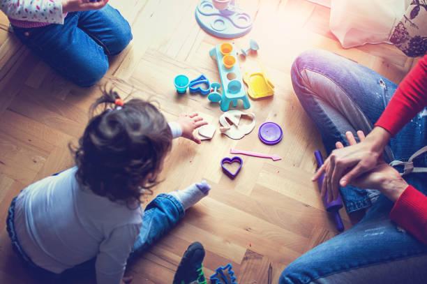 mutter und töchter spielen mit plastilin - knete spiele stock-fotos und bilder