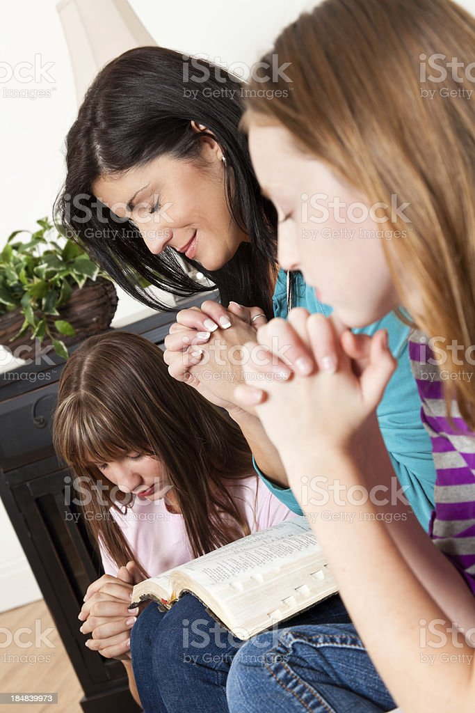 Mother and daughters praying during bible study at home royalty-free stock photo