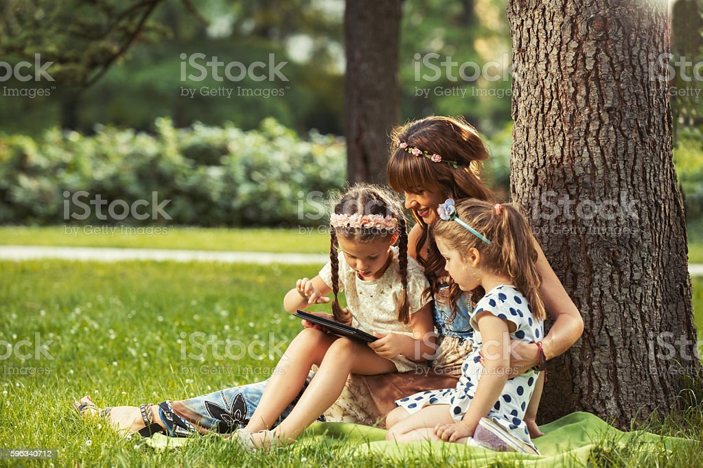 Mother and daughters sitting on grass using digital tablet. Lizenzfreies stock-foto