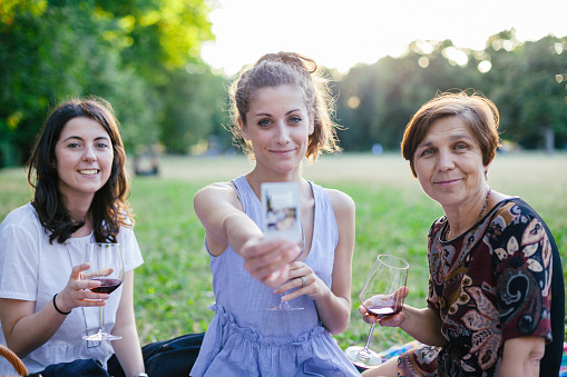 Mother and daughters take a instant photo at the park in summer during picnic. Young woman shows photo