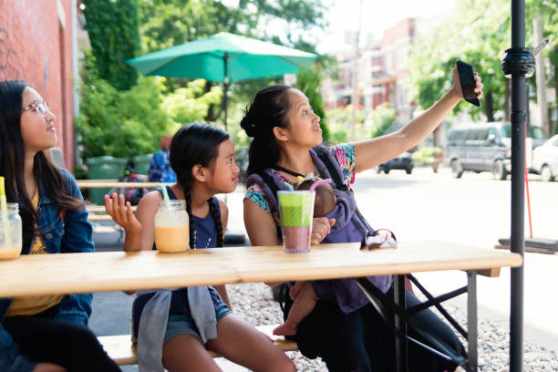 Mother and daughters taking a selfie outdoors on store terrace. stock photo