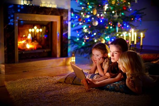 mother and daughters using tablet by a fireplace on christmas - cosy pillows mother child bildbanksfoton och bilder