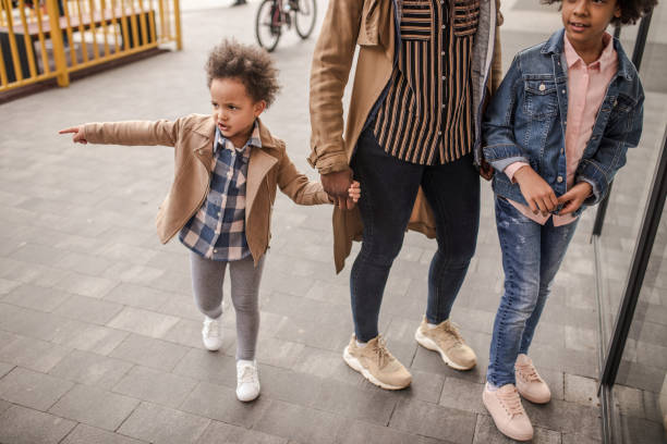 Mother and daughters window shopping at retail park stock photo