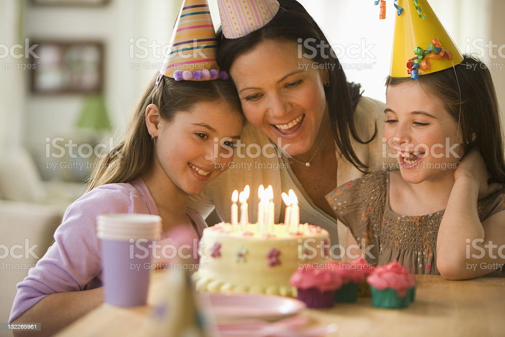 Mother and daughters with birthday cake royalty-free stock photo