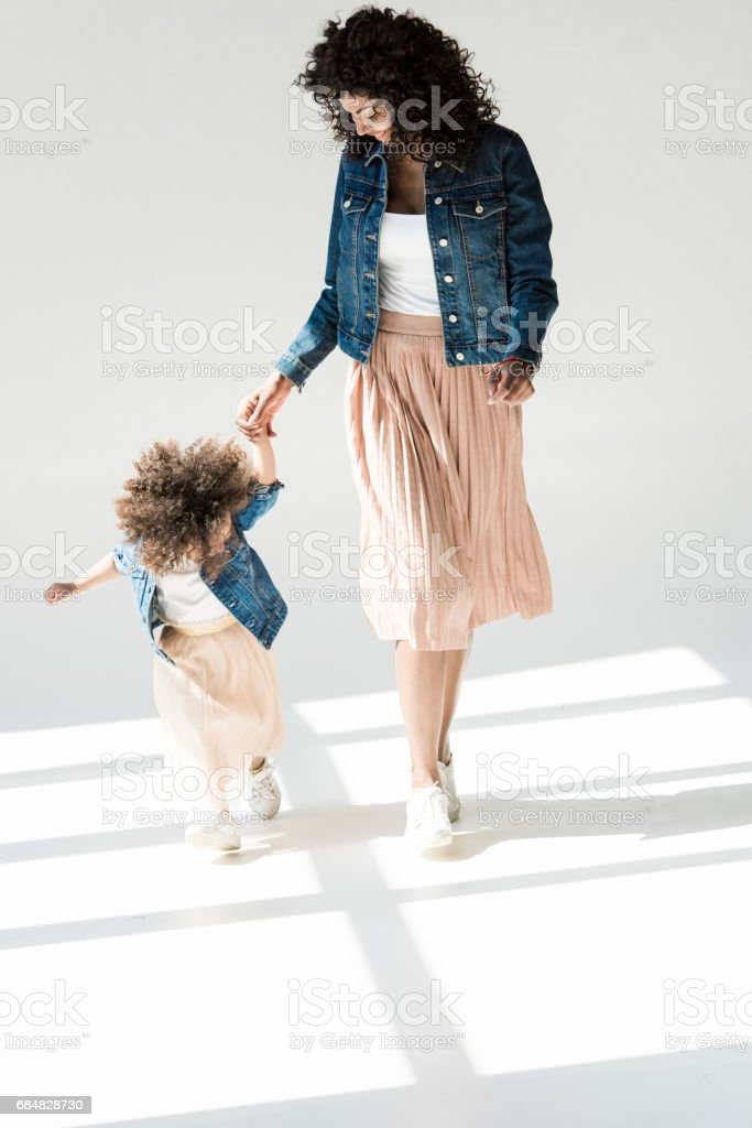 mother and daugter holding hands stock photo