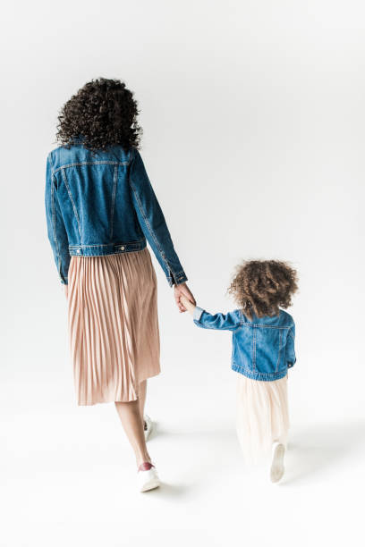 mother and daugter holding hands - skirt stock photos and pictures