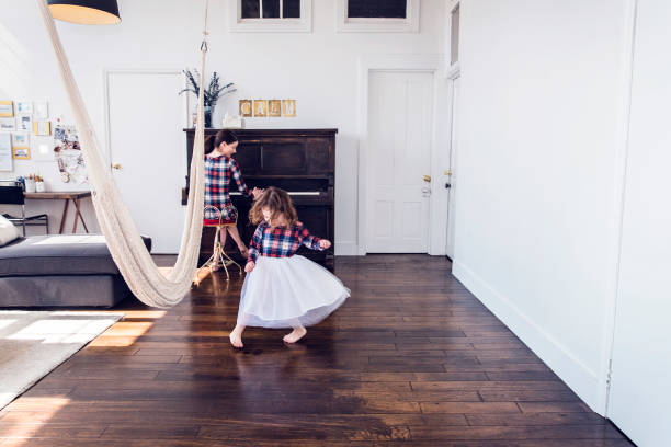 mor och dotter njuter av tonerna av ett upprätt piano på sin loftlägenhet - beautiful floor bildbanksfoton och bilder