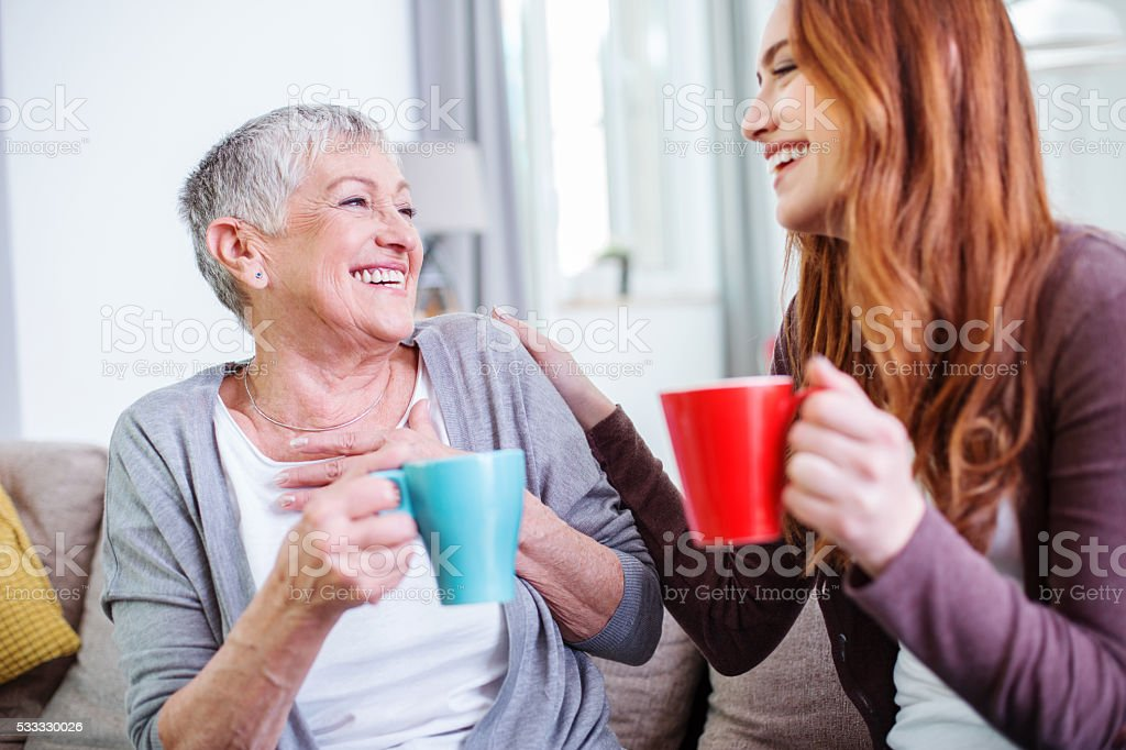 Mother and dauther having hot drinks together stock photo