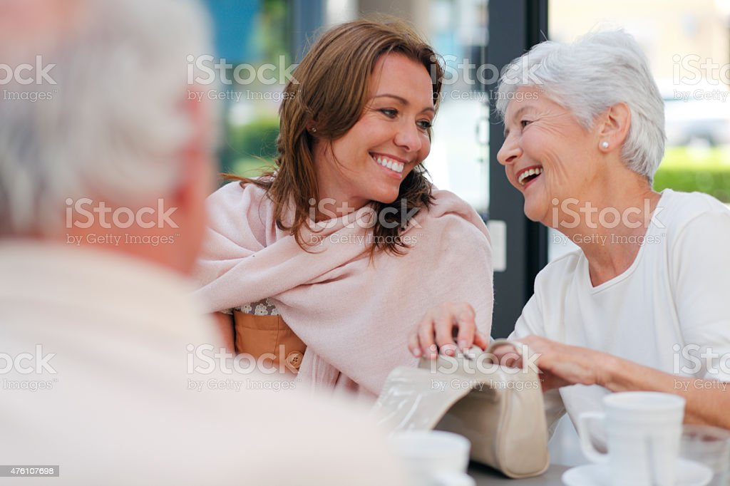 Mother and dauther smiling in a coffee shop stock photo