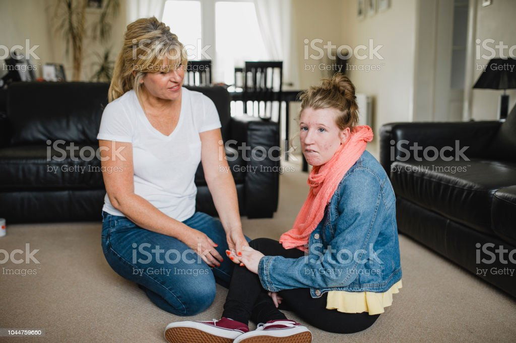 Mother and Disabled Daughter Relaxing at Home stock photo