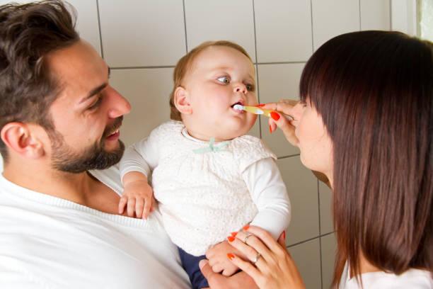 annem ve babam onların bebek diş fırçalama - baby teeth stok fotoğraflar ve resimler