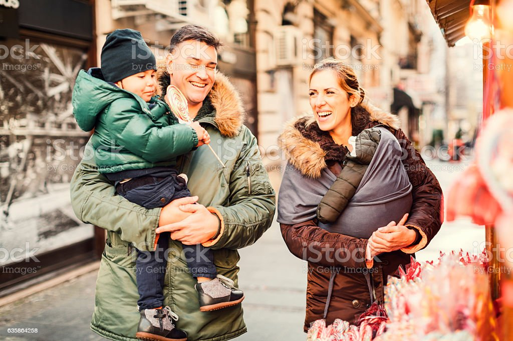 Mother And Father Buying Sweets To Their Son stock photo