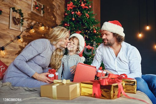Mother and father give a child a gift box in the house at Christmas