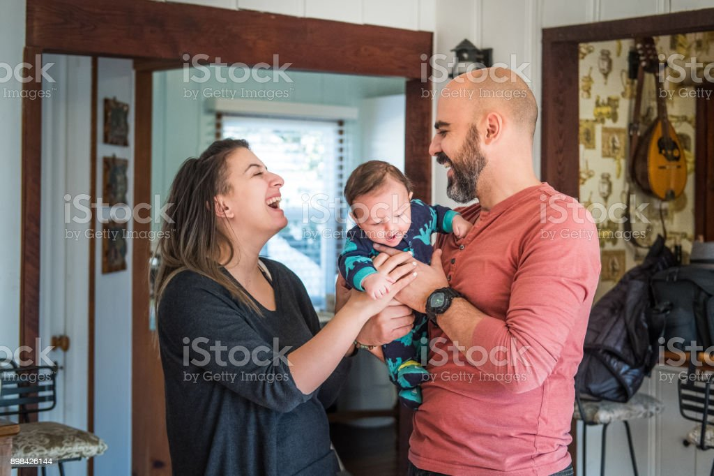 Mother and Father hold infant son stock photo