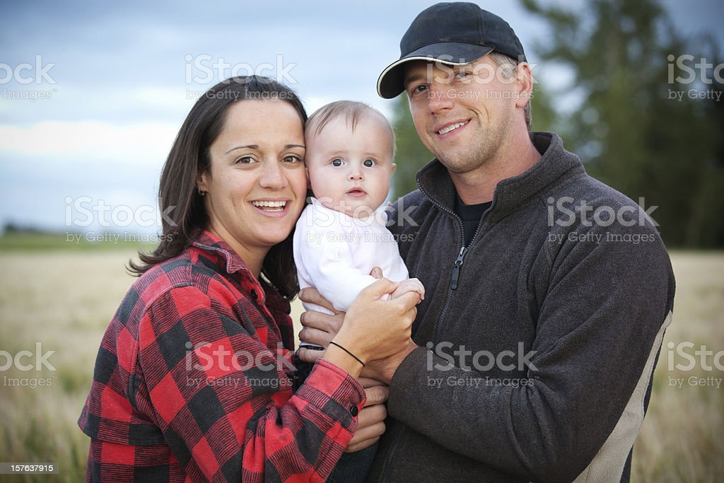 A mother and father holding their baby in a field stock photo