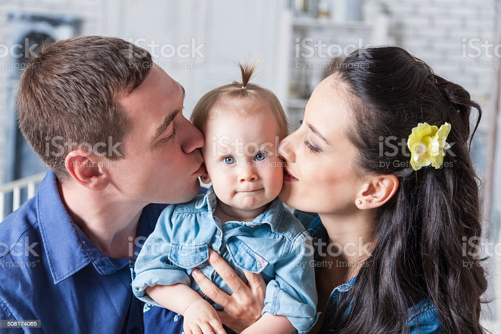 Mother and father kissing his year-old daughter stock photo