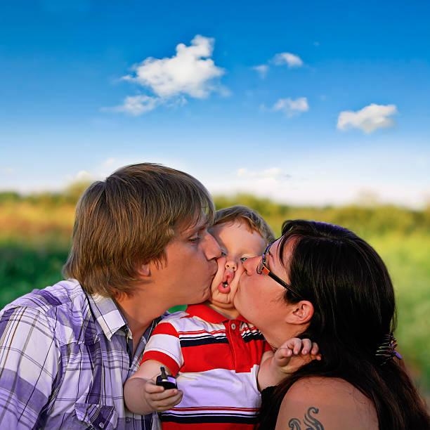 madre e padre baciare il figlio sulla guancia al di fuori - brunette woman eyeglasses kiss man foto e immagini stock